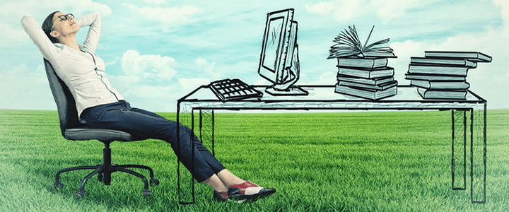 stock photo of woman sitting at drawn desk in grass