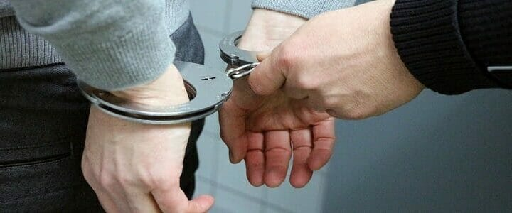 stock photo of handcuffs being put on man