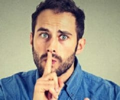 stock photo of man with finger to mouth saying shh