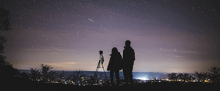 stock photo of people looking at stars over city