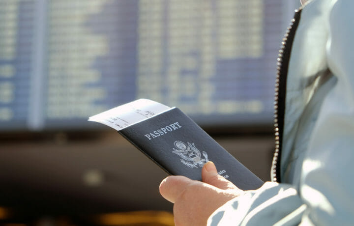Man holding passport and plane tickets are airport