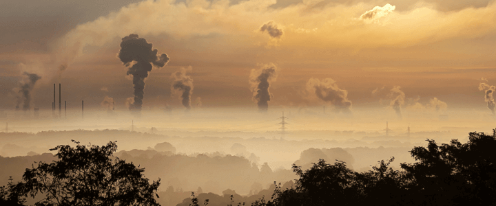 Photo of smokestacks and smoke on horizon at dawn