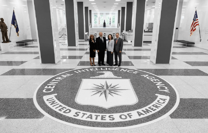 Man and three women standing on seal at CIA