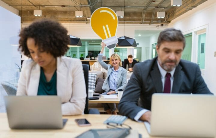Woman in background of office holding giant lightbulb over head