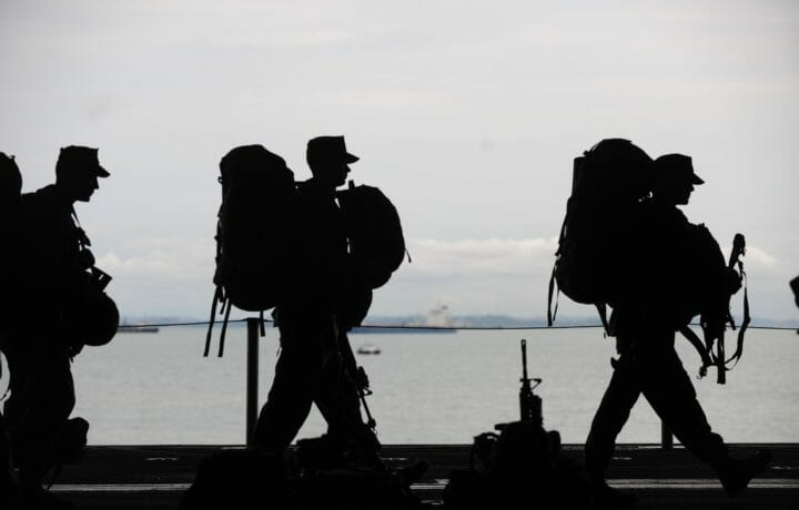 Silhouettes of three soldiers with large backpacks