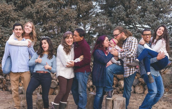 Photo of multi-generational family in front of log pile