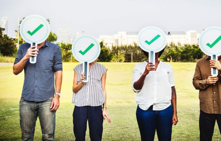 Four people with green check signs covering face