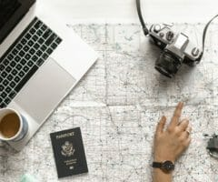 woman pointing on a map planning foreign travel with passport, camera, laptop and coffee