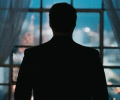 silhouette of a mysterious man in front of a window looking at a city at nighttime