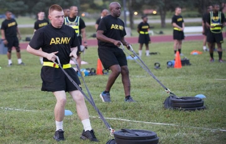ACFT two men dragging weights in field
